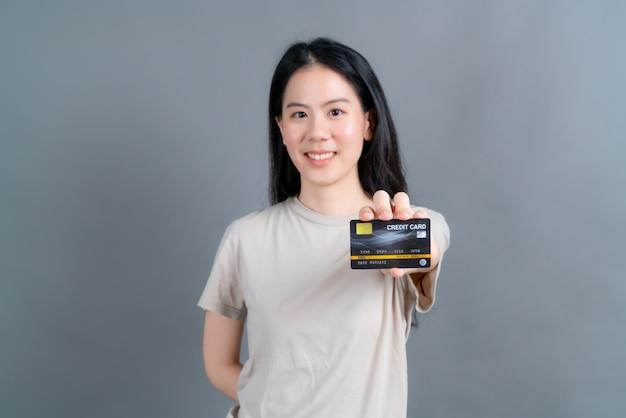 Portrait d'une belle jeune femme asiatique montrant la carte de crédit avec copie espace sur mur gris
