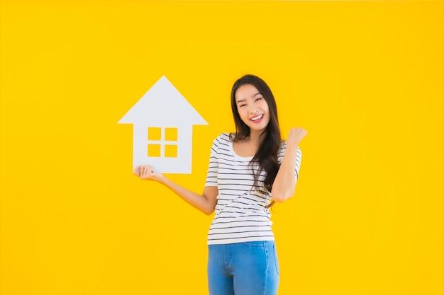 Portrait belle jeune femme asiatique montrer signe maison