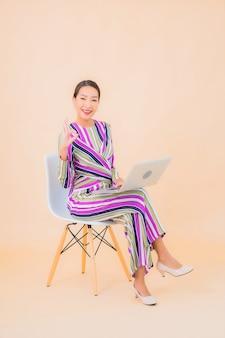 Portrait belle jeune femme asiatique avec ordinateur portable sur la couleur