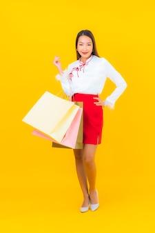 Portrait belle jeune femme asiatique avec panier et carte de crédit sur jaune