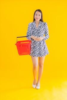 Portrait belle jeune femme asiatique avec panier d'épicerie pour faire du shopping sur jaune