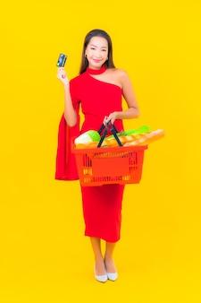 Portrait belle jeune femme asiatique avec panier d'épicerie de supermarché
