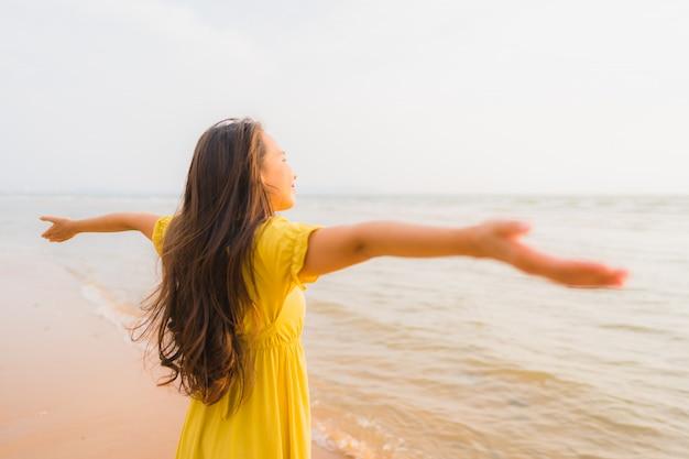 Portrait belle jeune femme asiatique à pied sur la plage et la mer