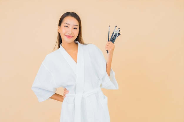 Portrait belle jeune femme asiatique avec pinceau de maquillage sur beige
