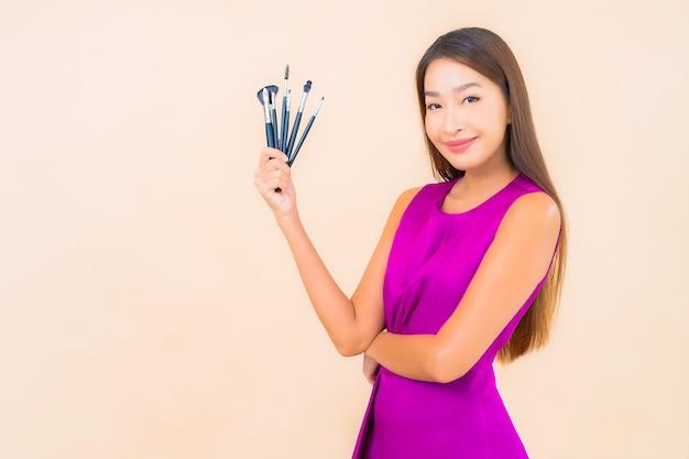 Portrait belle jeune femme asiatique avec pinceau de maquillage sur fond isolé de couleur