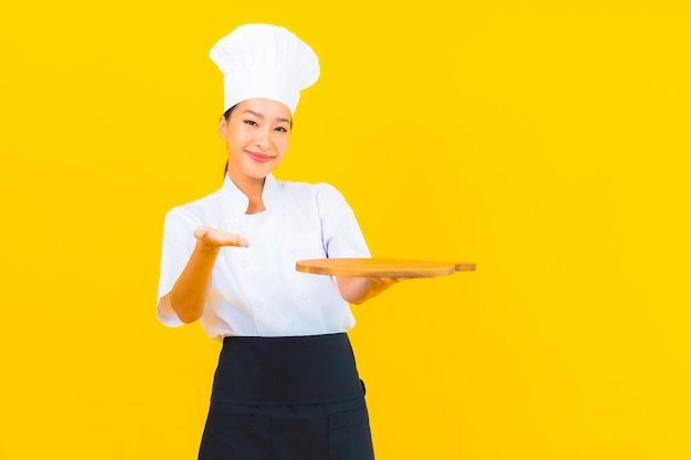 Portrait belle jeune femme asiatique avec planche à découper en bois sur fond isolé jaune