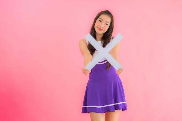 Portrait belle jeune femme asiatique pom-pom girl sourire montrer signe