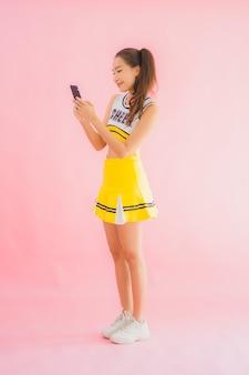 Portrait belle jeune femme asiatique pom-pom girl avec téléphone mobile intelligent