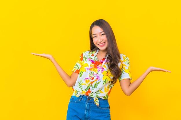 Portrait de la belle jeune femme asiatique portant une chemise colorée sur un mur jaune
