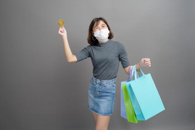Un portrait de la belle jeune femme asiatique portant un mak chirurgical tient une carte de crédit et un sac à provisions coloré isolé