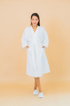 Portrait belle jeune femme asiatique portant peignoir avec sourire sur beige