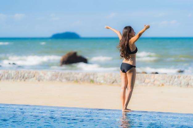 Portrait belle jeune femme asiatique porter un bikini autour de la piscine dans l'hôtel resort près de la mer océan plage