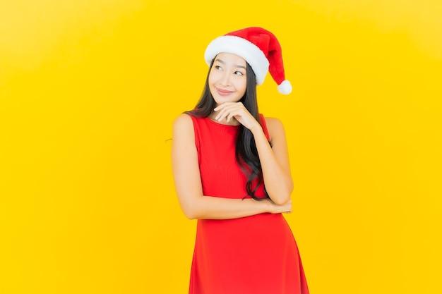 Portrait belle jeune femme asiatique porter bonnet de noel ou bandeau sur mur jaune