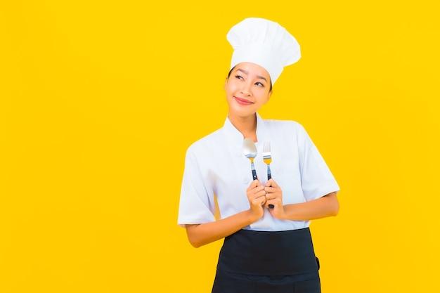 Portrait belle jeune femme asiatique porter un uniforme de chef ou de cuisinier avec cuillère et fourchette sur fond isolé jaune