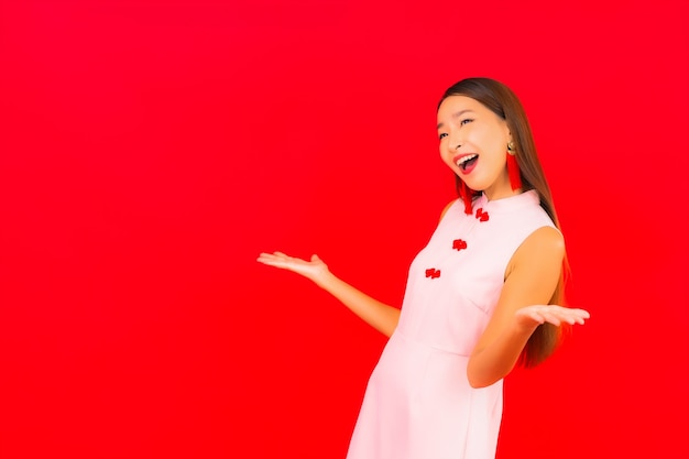 Portrait belle jeune femme asiatique porter des vêtements du nouvel an chinois sur mur rouge