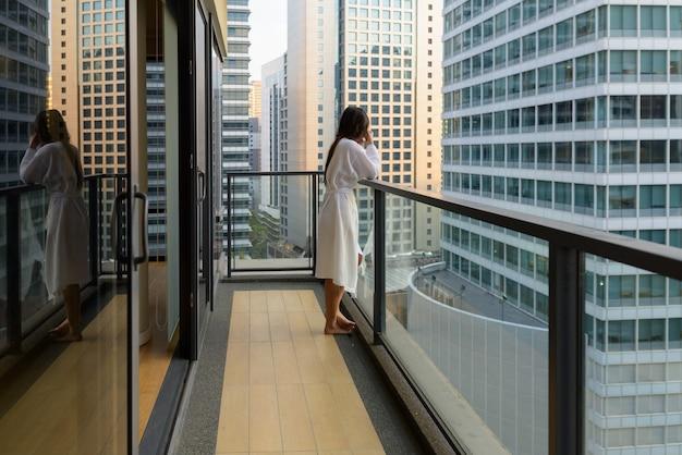 Portrait de la belle jeune femme asiatique profitant de la vue sur la ville depuis le balcon