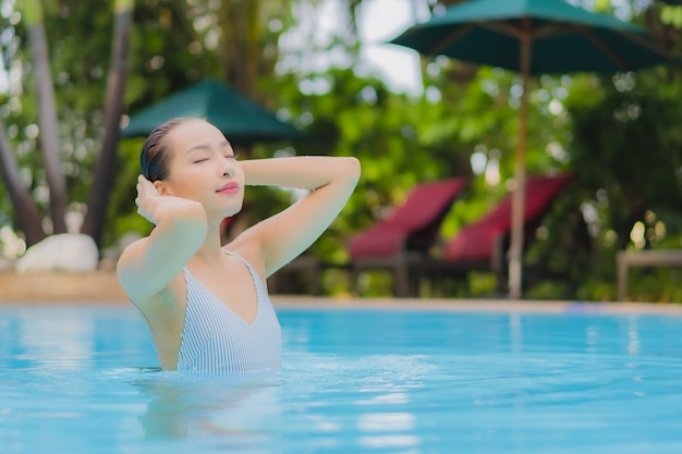 Portrait belle jeune femme asiatique profiter de se détendre sourire loisirs autour de la piscine extérieure dans l'hôtel