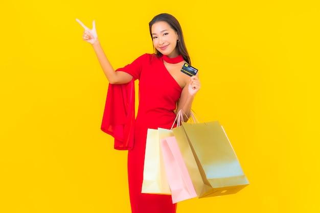 Portrait belle jeune femme asiatique avec sac à provisions et carte de crédit