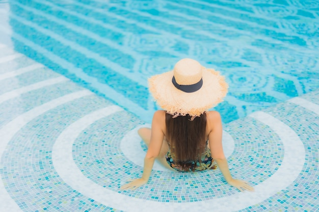 Portrait de la belle jeune femme asiatique se détend sur la piscine de l'hôtel resort