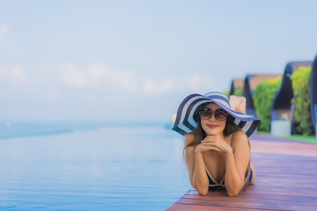 Portrait belle jeune femme asiatique se détendre autour de la piscine dans l'hôtel resort