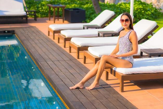 Portrait belle jeune femme asiatique se détendre autour de la piscine dans un hôtel de villégiature en vacances