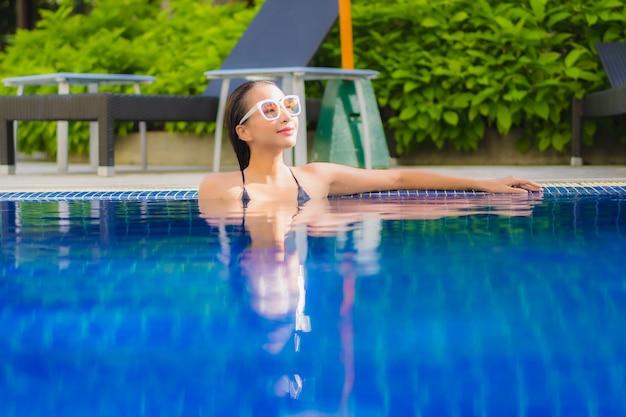 Portrait de la belle jeune femme asiatique se détendre autour de la piscine extérieure dans l'hôtel resort