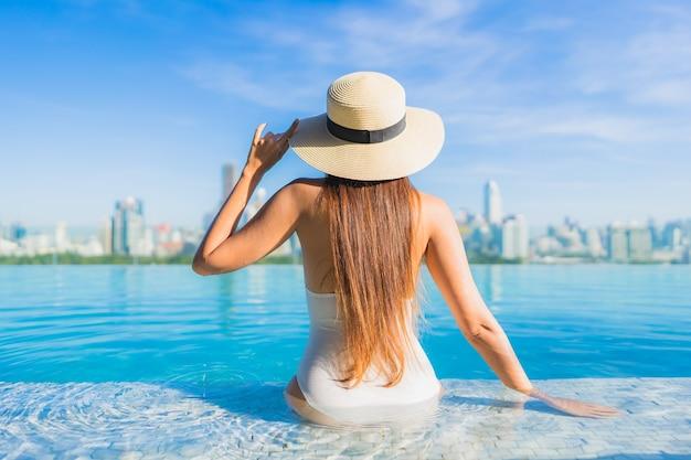 Portrait belle jeune femme asiatique se détendre autour de la piscine extérieure avec vue sur la ville