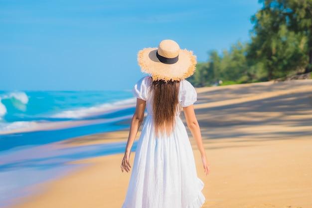 Portrait de la belle jeune femme asiatique se détendre autour de la plage avec des nuages blancs sur ciel bleu en vacances de voyage
