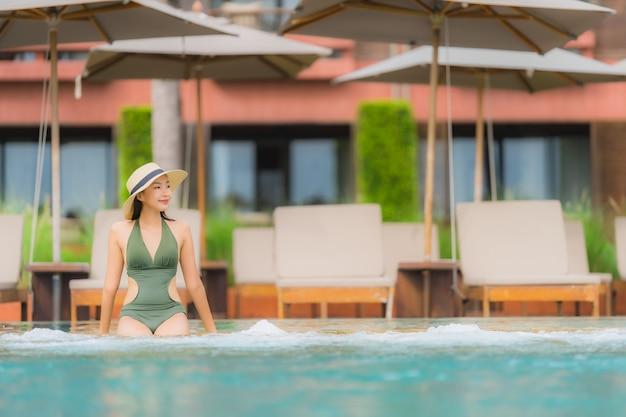 Portrait belle jeune femme asiatique se détendre dans la piscine extérieure de luxe dans l'hôtel resort près de la mer