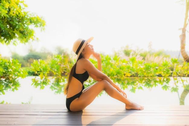 Portrait belle jeune femme asiatique se détendre dans la piscine de l'hôtel pour des vacances de loisirs