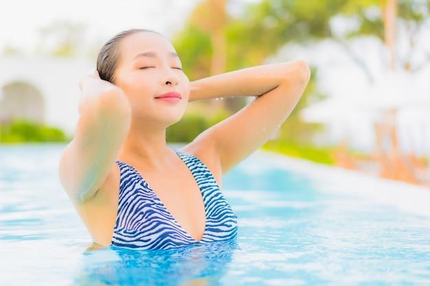 Portrait belle jeune femme asiatique se détendre les loisirs autour de la piscine extérieure avec mer océan plage