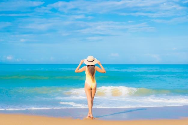 Portrait de la belle jeune femme asiatique se détendre sur la plage en vacances de voyage
