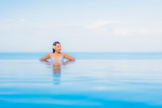 Portrait belle jeune femme asiatique se détendre sourire autour de la piscine extérieure dans l'hôtel resort
