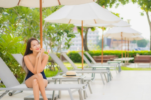 Portrait belle jeune femme asiatique se détendre sourire autour de la piscine extérieure dans la station de l'hôtel en voyage de vacances