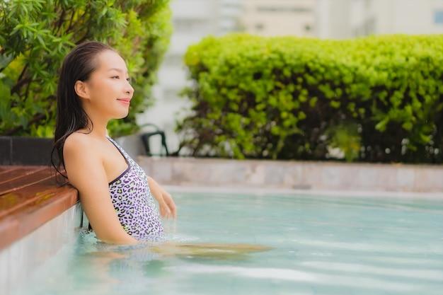 Portrait belle jeune femme asiatique se détendre sourire autour de la piscine extérieure pour les loisirs et les vacances