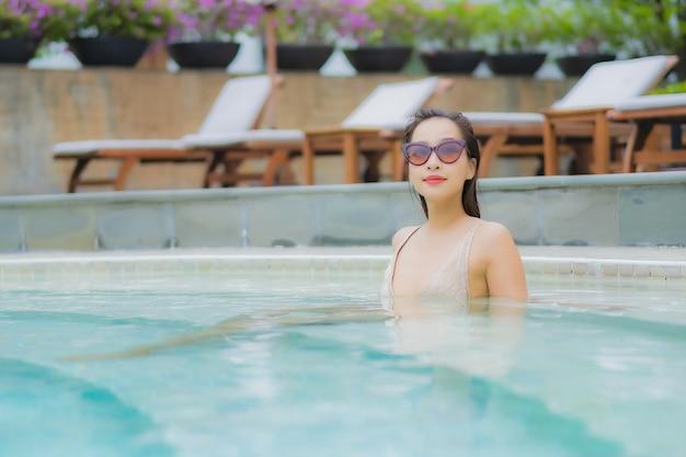 Portrait belle jeune femme asiatique se détendre sourire autour de la piscine extérieure