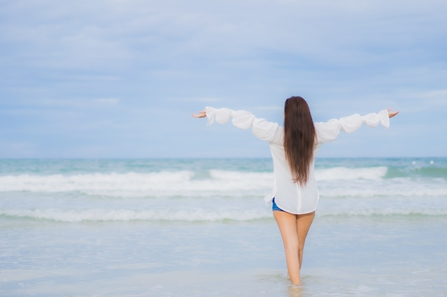 Portrait belle jeune femme asiatique se détendre sourire autour de la plage mer océan en vacances vacances voyage voyage