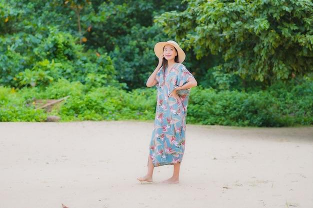 Portrait belle jeune femme asiatique se détendre sourire autour de la plage mer océan en vacances vacances