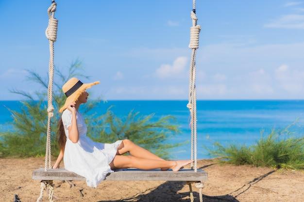 Portrait belle jeune femme asiatique se détendre sourire sur la balançoire autour de la plage mer océan pour la nature voyage en vacances