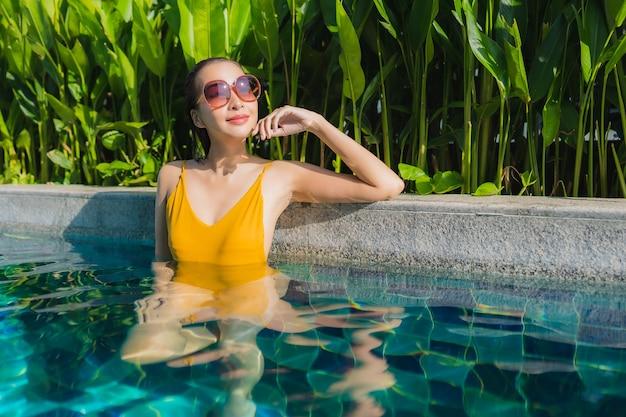 Portrait belle jeune femme asiatique se détendre sourire heureux autour de la piscine extérieure dans l'hôtel resort pour des vacances de loisirs