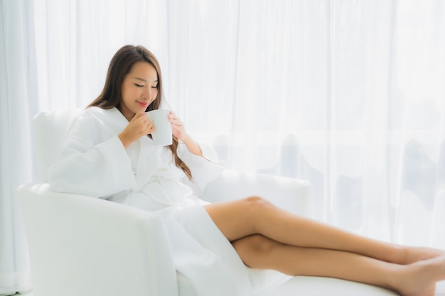 Portrait belle jeune femme asiatique se détendre sourire heureux avec une tasse de café sur le canapé