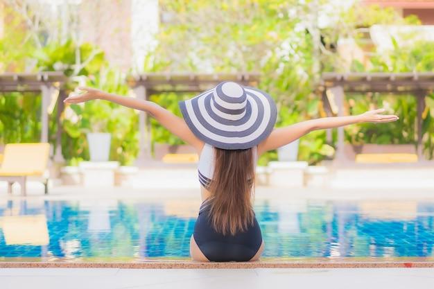Portrait belle jeune femme asiatique se détendre sourire loisirs autour de la piscine extérieure dans l'hôtel resort en vacances voyage
