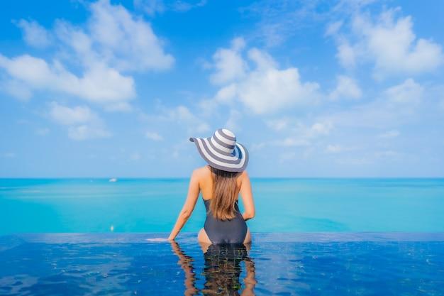 Portrait belle jeune femme asiatique se détendre sourire loisirs autour de la piscine extérieure dans un hôtel de villégiature avec vue mer océan