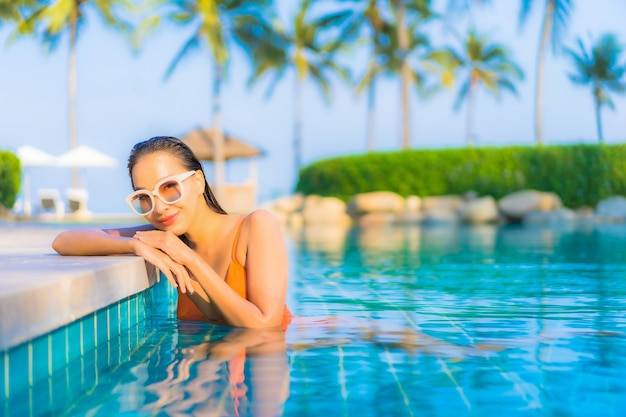 Portrait belle jeune femme asiatique se détendre sourire loisirs autour de la piscine extérieure avec vue sur l'océan mer