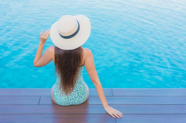 Portrait belle jeune femme asiatique se détendre sourire loisirs autour de la piscine extérieure