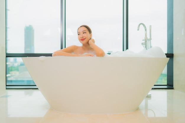 Portrait belle jeune femme asiatique se détendre sourire loisirs dans la baignoire à l'intérieur de la salle de bain