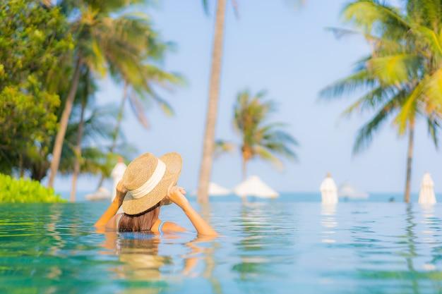 Portrait belle jeune femme asiatique se détendre sourire profiter de loisirs autour de la piscine près de la mer plage vue sur l'océan en vacances