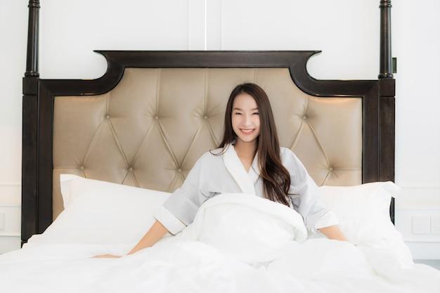 Portrait belle jeune femme asiatique se réveiller avec heureux et sourire sur le lit à l'intérieur de la chambre