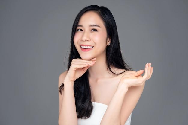 Portrait d'une belle jeune femme asiatique souriante sur fond gris