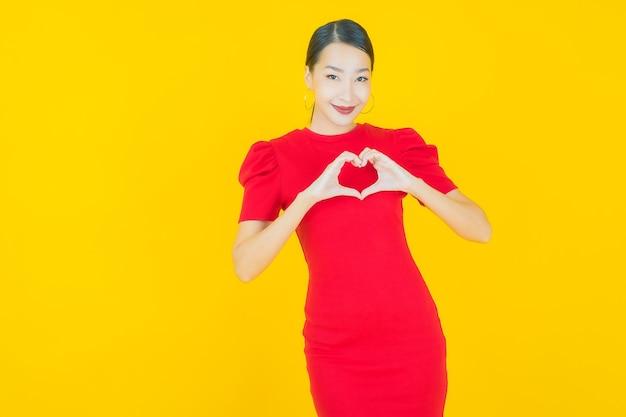 Portrait belle jeune femme asiatique sourire avec action sur jaune
